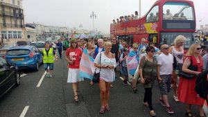 The Trans Pride march, people are holding trans flags, in the centre one person wears a 'some people are trans, get over it' shirt, next to someone wearing a shirt for mermaids UK. Spectators watch from the top desk of a bus parked along the seafront.